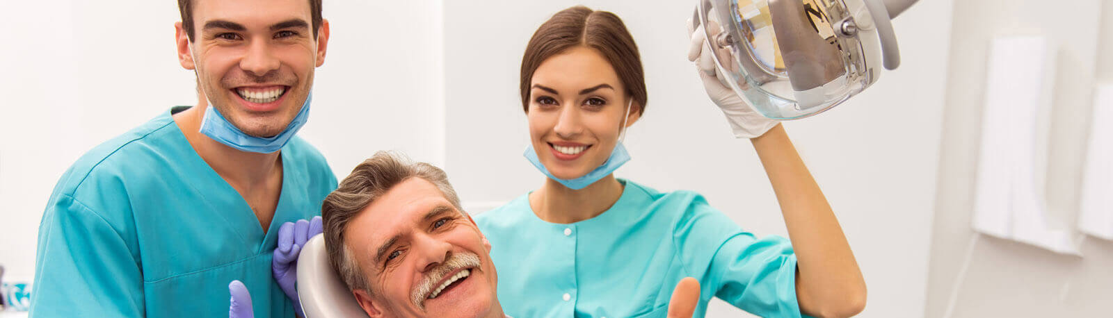 Young doctor dentist and his assistant, elderly patient smiling and looking at the camera